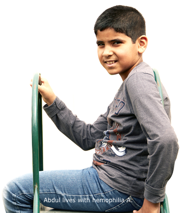 Profile view of Abdul, who lives with hemophilia A, sitting at the top of a slide, smiling and turned toward camera