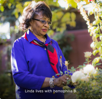 Linda, who lives with hemophilia B, standing in a flower garden and looking at a rose