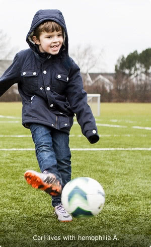 Carl, who lives with hemophilia A, outdoors, standing on a soccer field and kicking a soccer ball