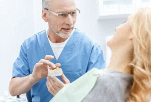 Closeup of female patient in examination chair facing away from camera with dentist talking to her and facing camera