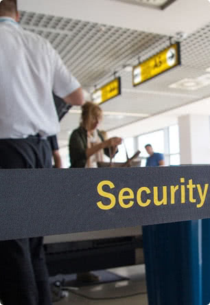 Airport signage saying Security with travelers in the background